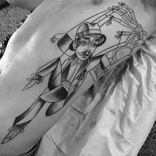 Татуировка кукловод на боку у парня