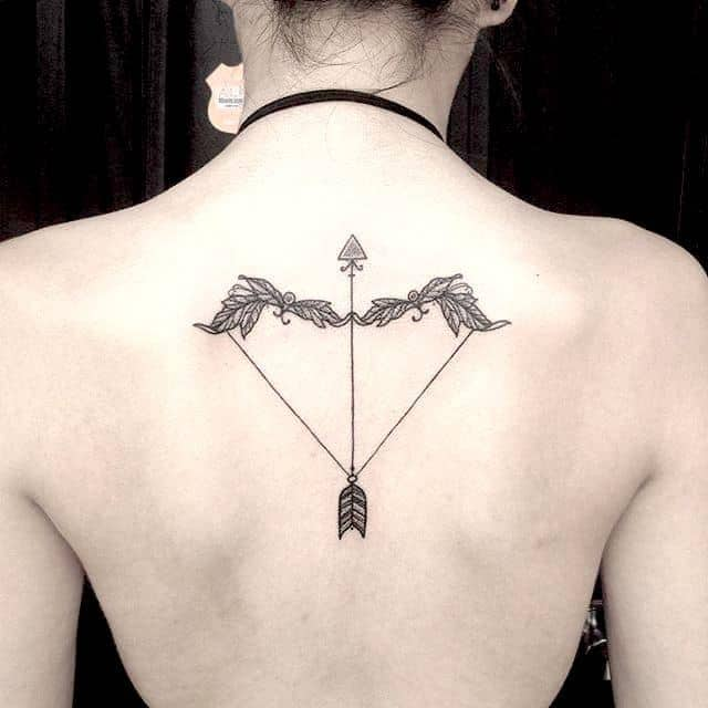 Татуировка лук и стрелы на спине у девушки