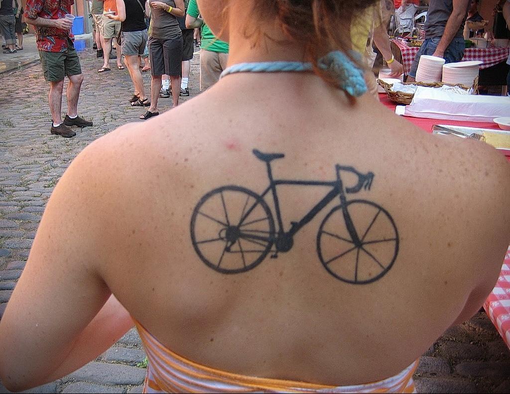 Тату велосипед между лопаток у девушки